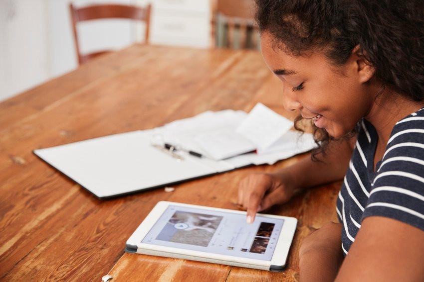 une jeune fille travaille sur une tablette numérique